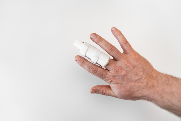 Orthosis for fixing the finger on hand on a white background. langet to heal the phalanxes of the fingers, due to injuries. orthopedic accessories. pharmacy and medical equipment.