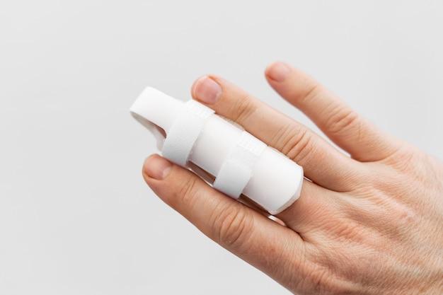 Ортез для фиксации пальца на руке на белом фоне. langet для заживления фаланг пальцев в результате травм. ортопедические аксессуары. аптека и медицинское оборудование.