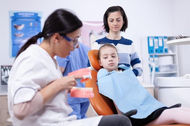 Ортодонт чистит щеткой искусственную челюсть, обучая ребенка, сидящего на стоматологическом кресле. маленькая девочка и мать, слушая стоматолога, говорят о гигиене зубов в стоматологической клинике, держа модель челюсти.