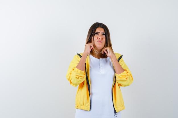 Ortrait di donna tappando le orecchie con le dita in t-shirt, giacca e guardando infastidito vista frontale