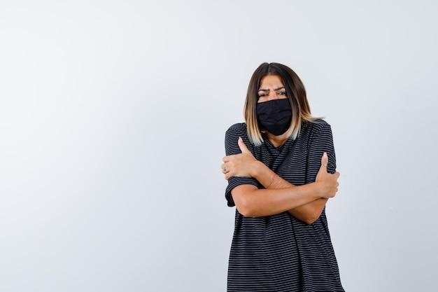 Ritratto di signora che si abbraccia o si sente freddo in abito nero, maschera medica e vista frontale sconvolta