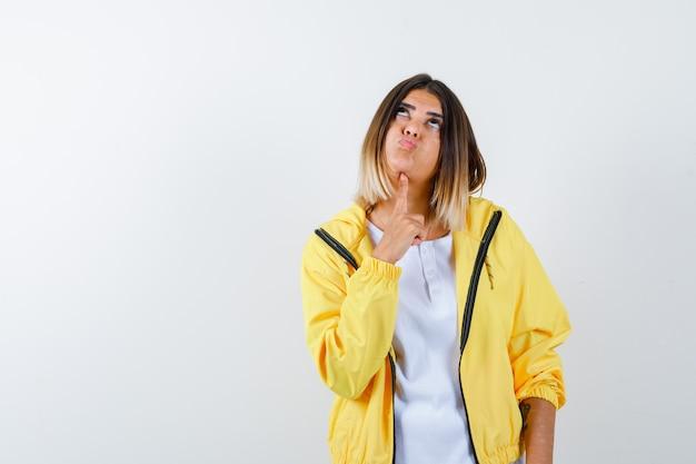 Ortrait di signora che tiene il dito sotto il mento in t-shirt, giacca e guardando premurosa vista frontale