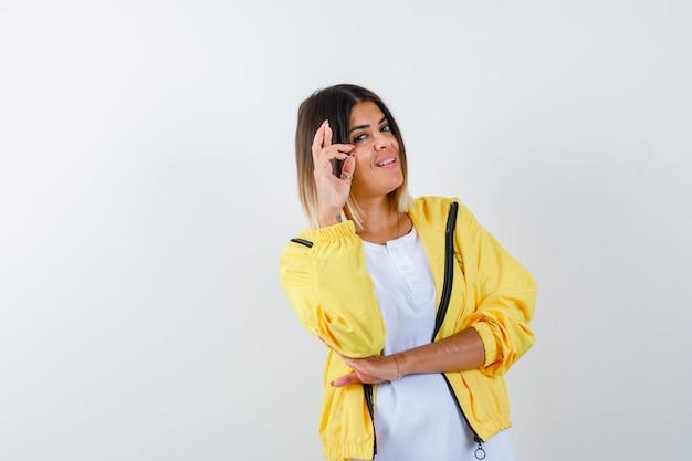 Ortrait di signora tenendo le dita incrociate in t-shirt, giacca e guardando allegra vista frontale