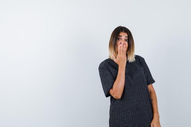 Ritratto di signora tenendo la mano sulla bocca in maglietta nera e guardando stupito vista frontale