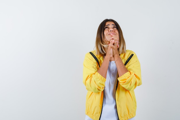 Ortrait of lady keeping hands in praying gesture in t-shirt, jacket and looking sorrowful front view