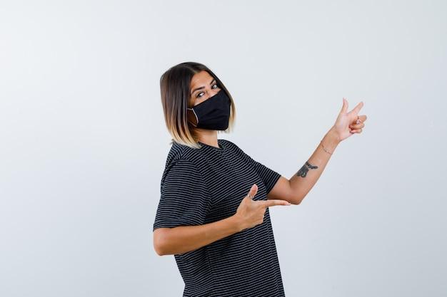 Ortrait di signora che punta a destra in abito nero, mascherina medica e guardando fiducioso vista frontale