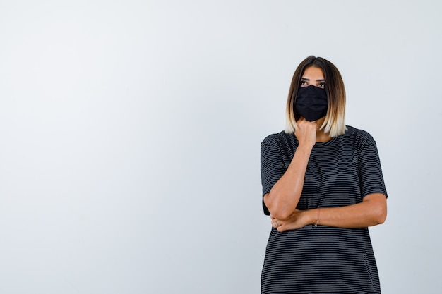 Ritratto di signora appoggiando il mento sul pugno in abito nero, maschera medica e guardando pensieroso vista frontale