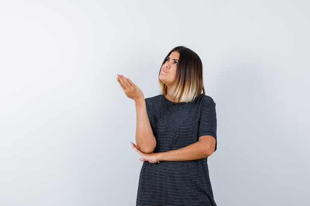 Ortrait di signora alzando la mano in modo interrogativo in maglietta nera e guardando perplesso vista frontale