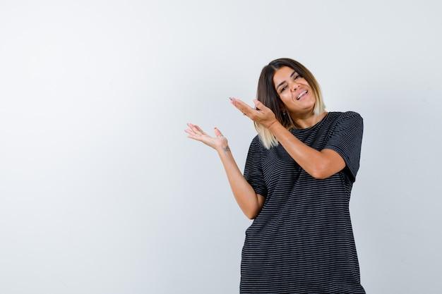 Ortrait di signora che mostra il gesto di benvenuto in maglietta nera e guarda vista frontale allegra