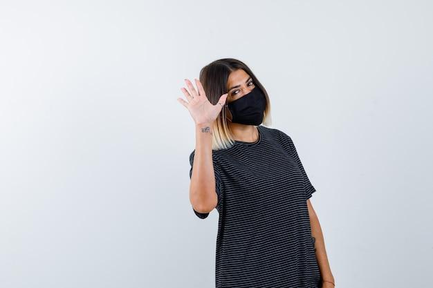Ritratto di signora agitando la mano per dire addio in abito nero, maschera medica e vista frontale allegra