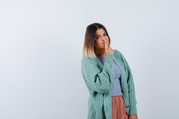Ортрайт женщины, демонстрирующей жест молчания в повседневной одежде и разумно выглядящей, вид спереди