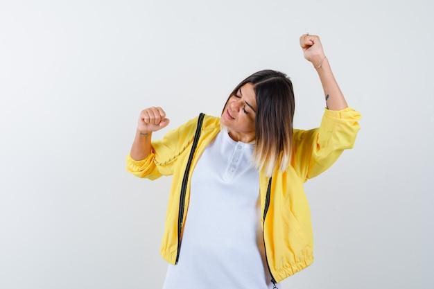 T- 셔츠, 재킷에 승자 제스처를 보여주는 여성의 ortrait 행복 전면보기를 찾고