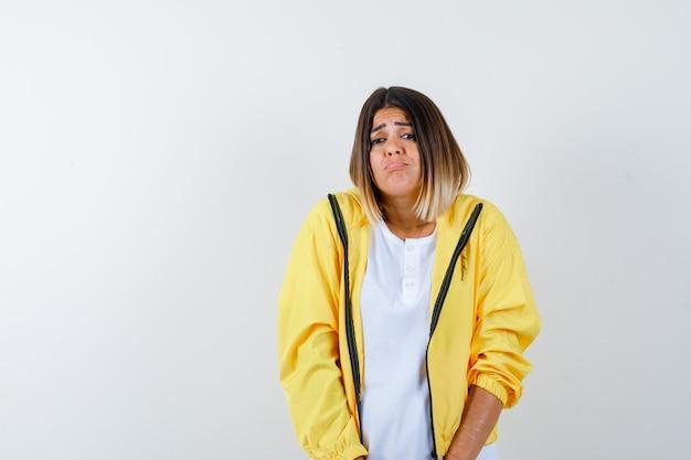 Ортрейт: хмурое лицо дамы, изогнутая нижняя губа в футболке, куртке и невинный вид спереди