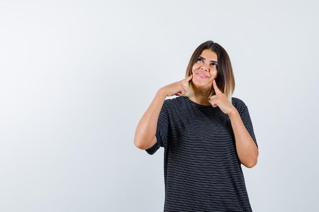 黒のtシャツで頬に指を置き、夢のような正面を見る女性のortrait
