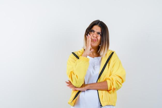 여자의 ortrait t- 셔츠, 재킷에 뺨에 손을 유지 하 고 혼란 스 러 워 전면보기