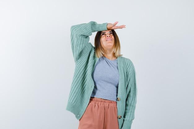 カジュアルな服装で頭を抱えて夢のような正面を見る女性のオルトレイト
