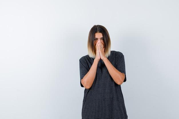 黒のtシャツで祈りのジェスチャーで手を保ち、希望に満ちた正面図を探している女性のortrait