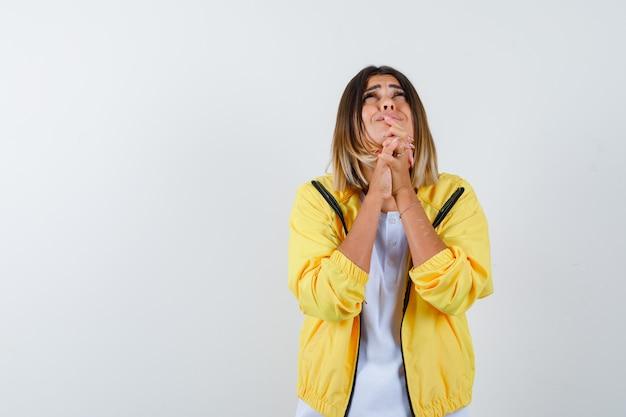 Ортрайт дамы, держащей руки в молитвенном жесте в футболке, куртке и печально выглядящей спереди