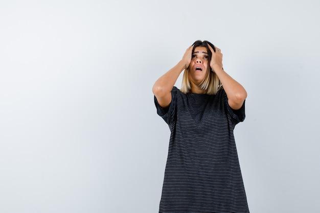 Ортрейт дамы, держащей руки за голову в черной футболке и выглядящей встревоженной, вид спереди