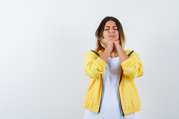 T- 셔츠, 재킷에 턱 아래에 손을 유지하고 슬픈 전면보기를 보는 숙녀의 ortrait
