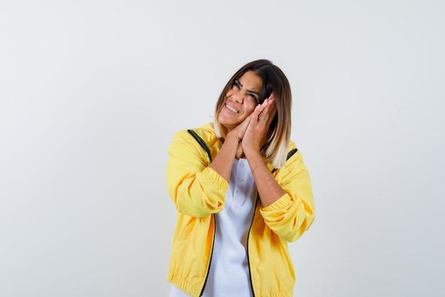 Tシャツ、ジャケットの枕として手のひらに寄りかかって幸せそうな正面図を探している女性のortrait