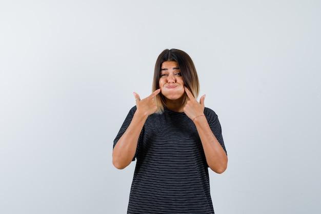 검은 티셔츠에 날아간 뺨을 가리키고 재미있는 정면보기를 바라 보는 숙녀의 ortrait