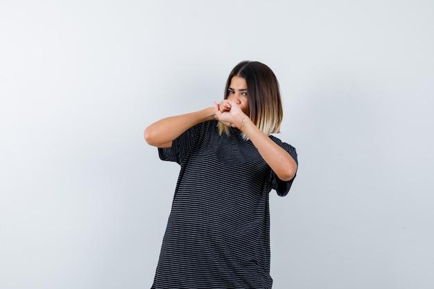 검은 티셔츠에 주먹을 들고 자신감을 보이는 여성의 ortrait