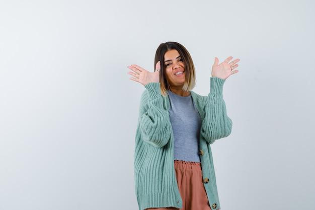 カジュアルな服装で降伏ジェスチャーで手のひらを示し、幸せな正面図を探している女性のortrait