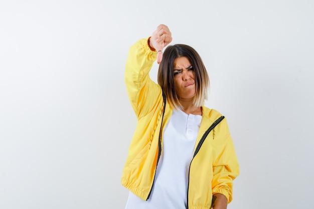 여자의 ortrait t- 셔츠, 재킷 아래로 엄지 손가락을 보여주는 불쾌한 전면보기