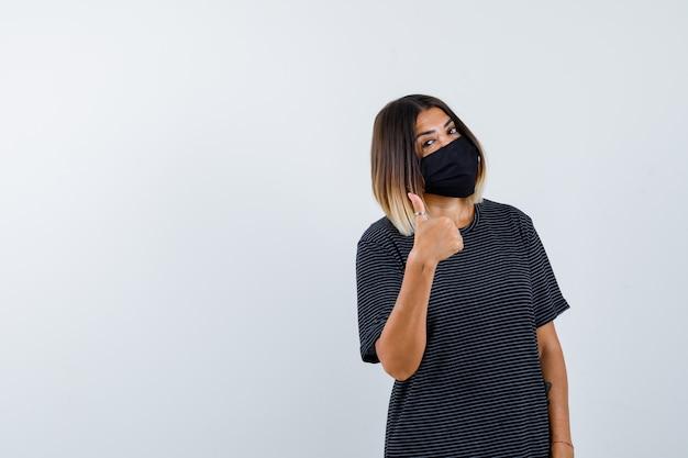 Ортрейт дамы, показывающей большой палец в черном платье, медицинской маске и уверенно выглядящей спереди