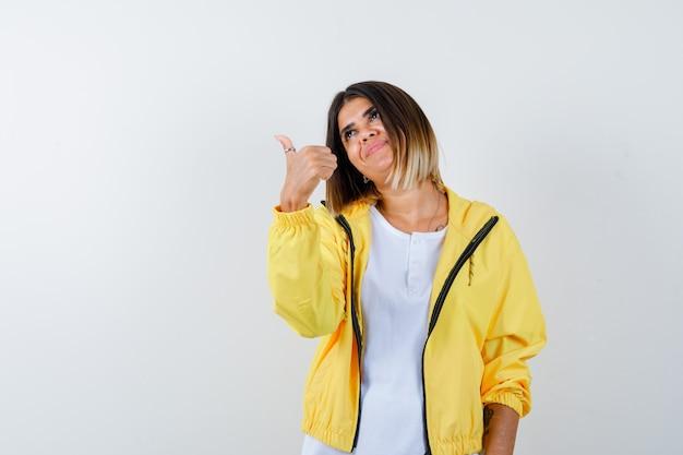 Ортрейт дамы показывает большой палец вверх в футболке, куртке и выглядит веселой вид спереди