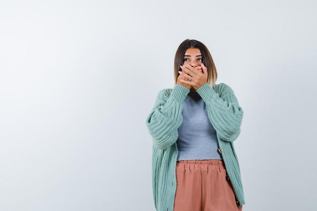 Ортрайт женщины, держащей руки во рту в повседневной одежде и испуганной, вид спереди