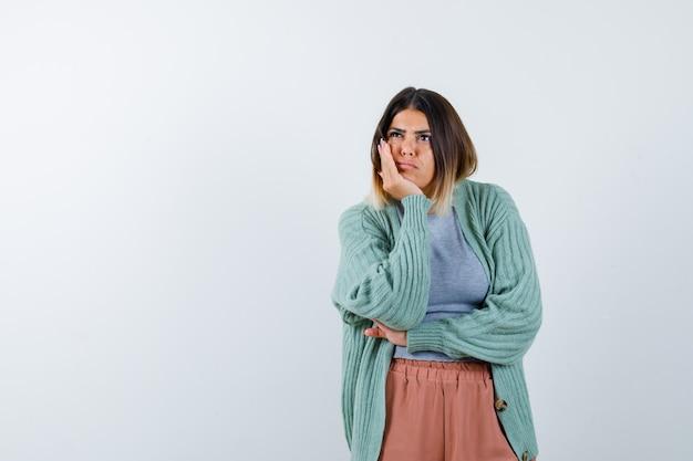 カジュアルな服装で手のひらに顎をもたれ、思慮深い正面を見る女性のortrait