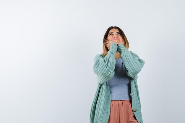 Ортрайт женщины, положившей лицо на руки в повседневной одежде и выглядящей веселой, вид спереди Бесплатные Фотографии