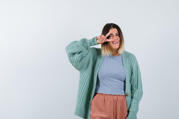 カジュアルな服装でvサインを目で見て楽しい正面を見る女性のortrait