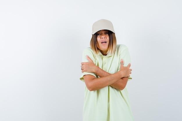 T- 셔츠, 모자에 자신을 포옹 하 고 냉장 된 전면보기를 찾고 젊은 여성의 ortrait