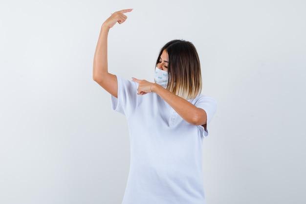 T- 셔츠, 마스크 옆으로 가리키는 자신감 전면보기를 찾고 젊은 여성의 ortrait