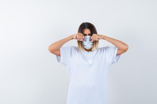 티셔츠, 마스크에 눈을 문지르고 불쾌한 정면보기를 보는 젊은 여성의 ortrait