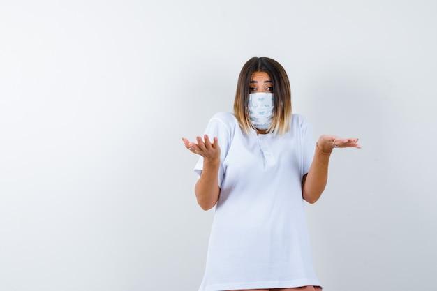 티셔츠, 마스크에 무력한 제스처를 보여주는 젊은 여성의 ortrait 및 의아해 전면보기