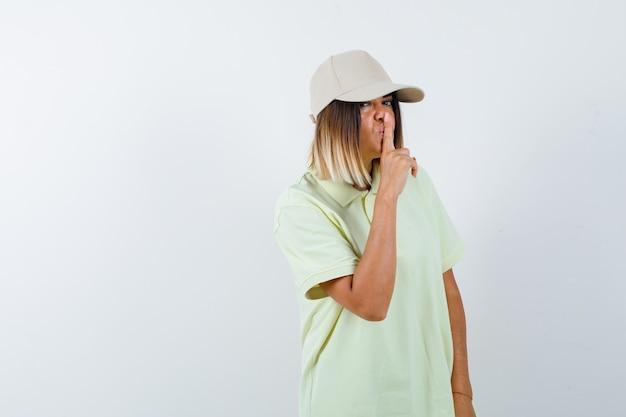 티셔츠, 모자에 침묵 제스처를 보여주는 젊은 여성의 ortrait 및 심각한 전면보기를 찾고