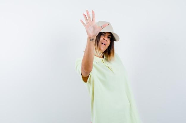 티셔츠, 모자에 정지 제스처를 보여주는 젊은 여성의 ortrait 및 심각한 정면보기