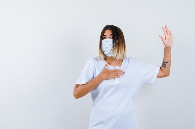 T- 셔츠, 마스크에 정지 제스처를 보여주는 젊은 여성의 ortrait 및 심각한 전면보기를 찾고
