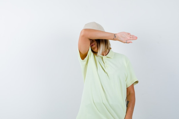 T- 셔츠, 모자에 그녀의 팔꿈치에 이마를 베개하고 피곤한 정면보기를 찾고 젊은 아가씨의 ortrait