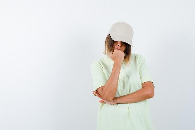 생각에 서있는 젊은 아가씨의 ortrait 티셔츠, 모자에 포즈와 사려 깊은 전면보기를 찾고