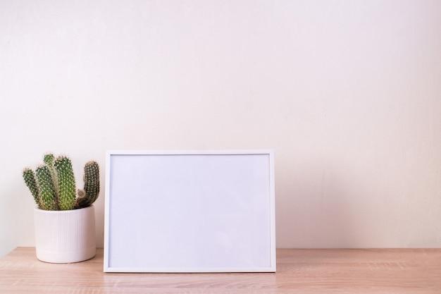 木製のテーブルのortrait白い額縁モックアップ。カスミソウと現代のセラミック花瓶。白い壁の背景。スカンジナビアのインテリア。