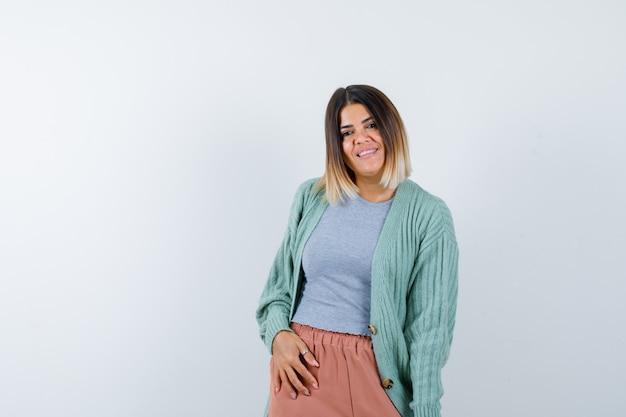 Ortrait di donna in posa stando in piedi in abiti casual e guardando felice vista frontale