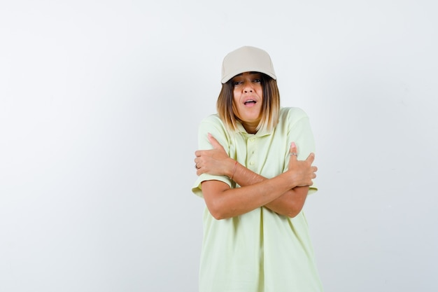 Ortrait di giovane donna che si abbraccia in t-shirt, berretto e guardando vista frontale refrigerata