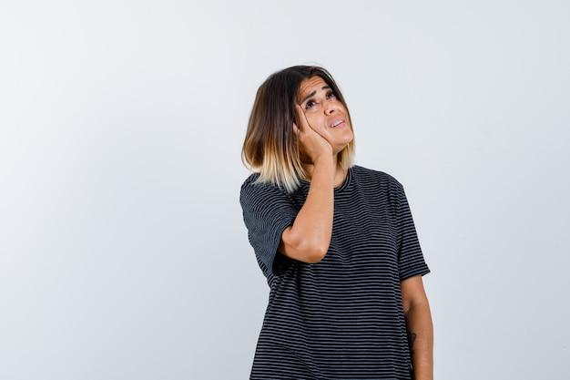 Ortrait di giovane donna che tiene la mano sulla guancia mentre cerca in abito polo e guardando confuso vista frontale