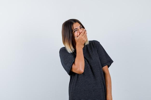 Ortrait di giovane donna che tiene la mano sulla bocca in abito polo e guardando allegro vista frontale