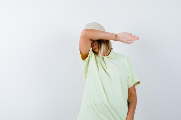 Ortrait di giovane donna che fa cuscino sulla fronte sul gomito in t-shirt, berretto e sembra stanco vista frontale